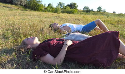 Dolly shot of young couple in love lying on green grass at field and stroking their siberian husky dog at sunny day. Happy pair relaxing and enjoying summer weekend at sunset. Low angle view Close up