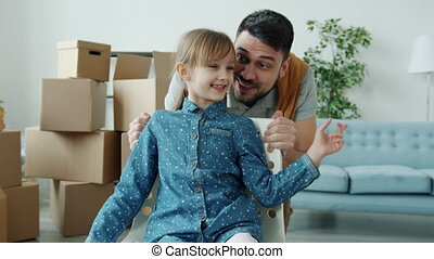Dolly shot of young man riding little girl in chair talking to daughter showing new apartment during relocation. Parenthood and housing concept.