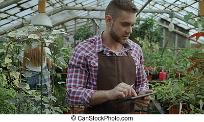 Dolly shot of Young man working in garden center. Attractive guy check and count flowers using tablet computer during work in greenhouse