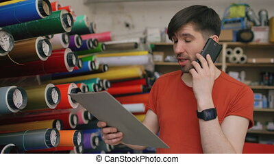 Dolly shot of Young worker in warehouse talking smartphone and checking inventory. Man works in sales department of advertising materials