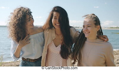 Dolly shot slow motion portrait of happy women multi-ethnic group walking outdoors on beach talking smiling enjoying summer day together