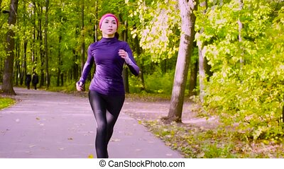 Young woman running in the park. Fitness - Dolly shot, slow...