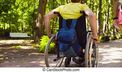 Wheels of a wheelchair and woman's legs during the walk