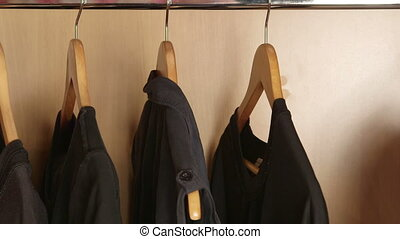 Dolly: Some black and one white t-shirt on a hangers in wardrobe