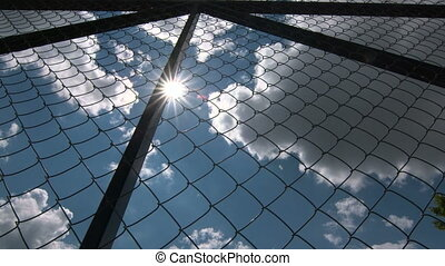 Dolly: Sun shining through the chain link iron wire fencing