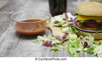 Dolly track of home made hamburger with fries on wooden table