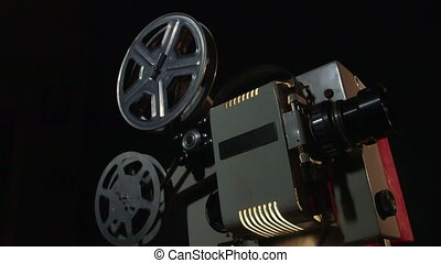 Dolly: Vintage 16 mm movie projector projecting film in a...