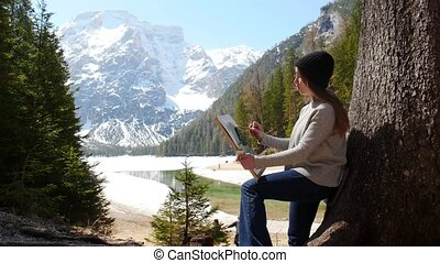 Dolomites. A young woman drawing a painting leaning on the tree