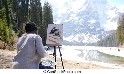 Dolomites. A young woman drawing mountains and forest on a...