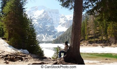 Dolomites. A young woman drawing on a canvas leaning on the tree