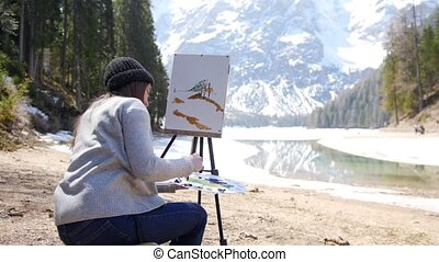 Dolomites. A young woman drawing on a canvas on an easel....