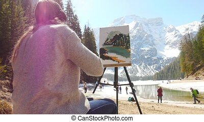 Dolomites. A young woman sitting on the coast of the river...