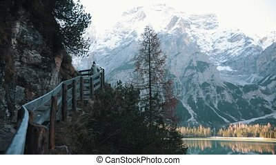 Dolomites. Mountain road. A woman walks upwards holding onto...