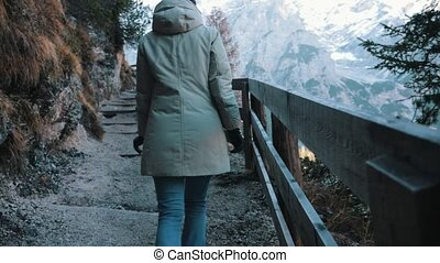Dolomites. Mountain road. A young woman walks upwards. Wide...