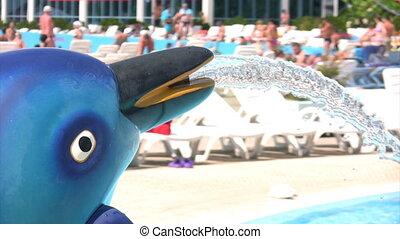 dolphing fountain in aqua park, defocused people