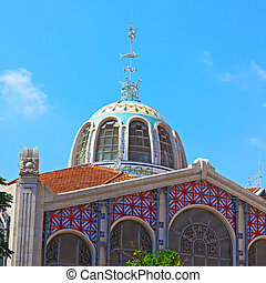 Dome exterior of Central Market (Mercado Central) in Valencia, Spain. Ornate Dome with colorful ceramics tiles, glass, marble and stone under blue sky with clouds.