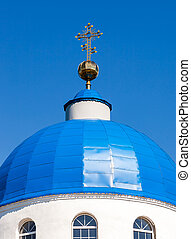 Dome of Russian orthodox church with golden cross against the blue sky