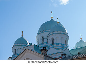 Domes of an Orthodox church against a blue sky on a sunny afternoon