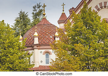 Domes of Our Lady of the Sign Church, the orthodox church between trees in Vilnius, Lithuania