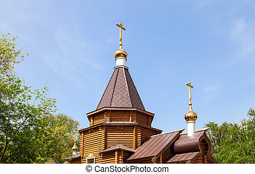 Domes of the wooden orthodox church against blue sky