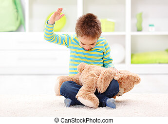 Domestic Abuse - Angry little boy beating his teddy bear -...