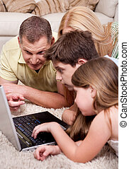 Domestic family of four lying and working with laptop
