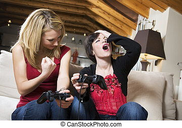domestic life - girls having fun with a new videogame