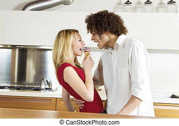 domestic life: interracial couple eating an ice cream