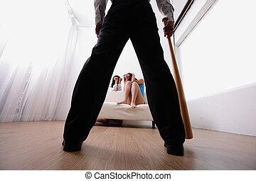 domestic violence - man holding baseball bat look his family...