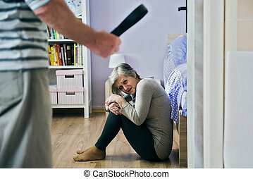 Domestic violence - Mature woman siiting on the floor is...