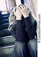 selective focus image of woman sit and holding her head