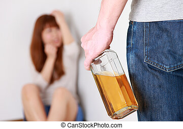 domestic violence - studio shot of alcoholic and his victim...