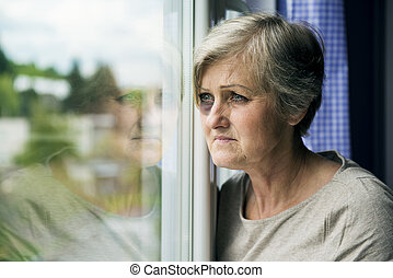 Domestic violence - Scared woman is looking through the...