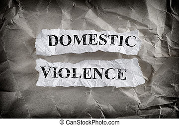 Torn pieces of paper with the words Domestic Violence written on them on crumpled paper background
