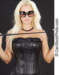 dominatrix in black leather corset with riding crop