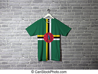Dominica flag on shirt and hanging on the wall with brick pattern wallpaper.