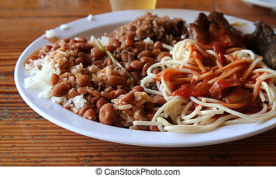 A lunch from the Dominican Republic featuring, beans, rice, spaghetti, chicken and beer. (cervasa)