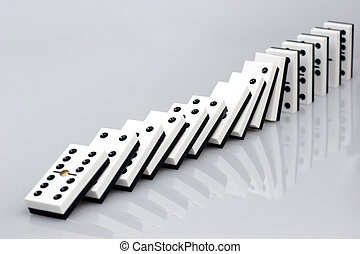 Domino effect - Dominos falling down in chain reaction