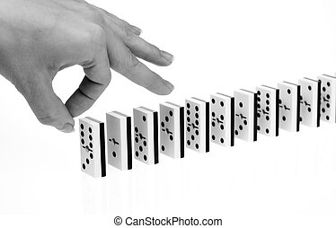Domino effect - Hand ready to start domino chain reaction,...