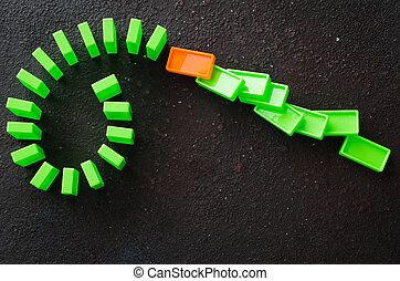 Domino effect - row of green dominoes on dark background. The concept of a weak link.