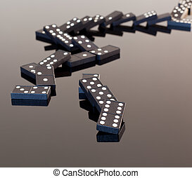 Macro image of dominos on a black reflactive surface and collapsed in pile