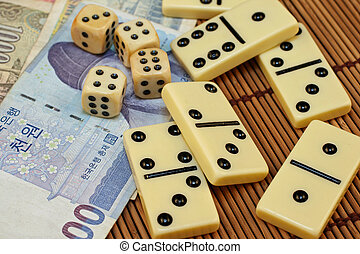 Dominoes, Korean money and dice on a bamboo mat