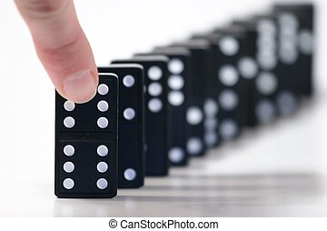 Dominoes - Finger ready to push over domino. Only the first...