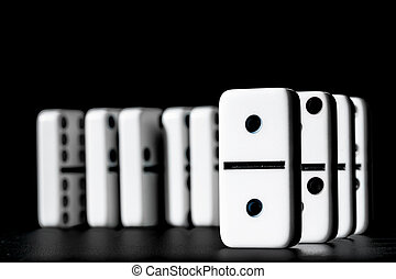 Dominoes standing in a row on black background