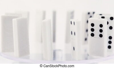 Dominoes with black dots stand vertically on glass and...