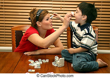 Child and teen playing with dominos at kitchen table.