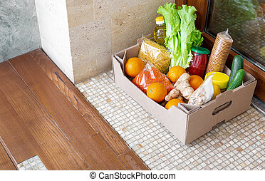 Donation Box with food during covid quarantine. Food box delivery on doorstep near door. Contactless social home delivery, safe shopping in coronavirus pandemic. Takeout meal. Courier home delivery