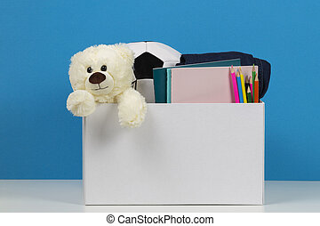 Donation box with toys, books, clothing for charity over blue background