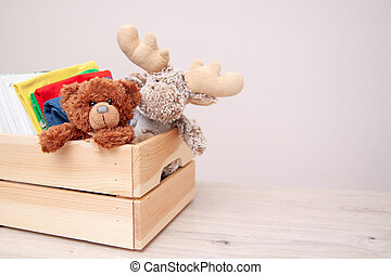 Donation concept. Donate box with kids clothes, books, school supplies and toys. Teddy bear and moose toy. Copyspace for text.