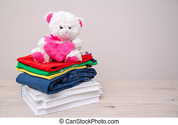 Donation concept. Donate goods with kids clothes, books, school supplies and toys. Teddy bear with big pink heart in hands. Copyspace for text.